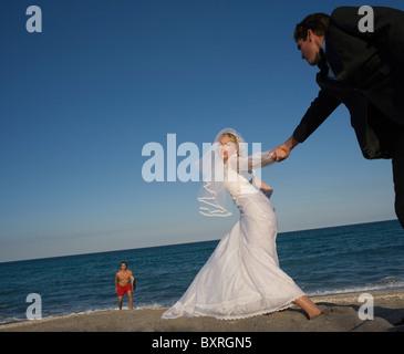 Braut und Bräutigam Hand in Hand am Strand Rettungsschwimmer im Hintergrund - Stockfoto
