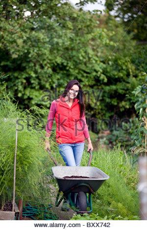 Eine junge Frau auf einer Zuteilung Schubkarre - Stockfoto