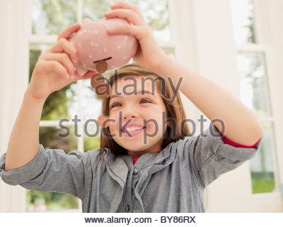 Aufgeregt Mädchen entleeren Münzen von Sparschwein - Stockfoto