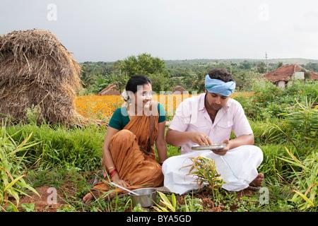 Ländliche Mann beim Mittagessen, als seine Frau schaut auf - Stockfoto