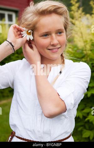 Porträt von Teenager-Mädchen setzen Blume im Haar - Stockfoto
