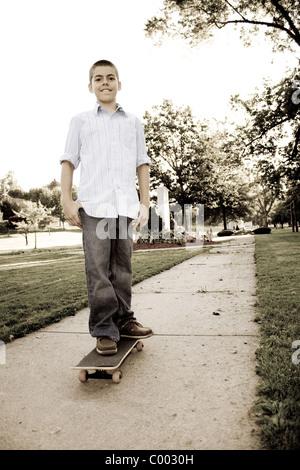 Ein junger Teenager auf seinem Skateboard im Park stehen. Sepia-Farbton. - Stockfoto