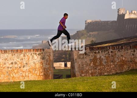 Ein kleiner Junge verlaufen entlang der alten Festungsmauer von San Juan, Puerto Rico. - Stockfoto