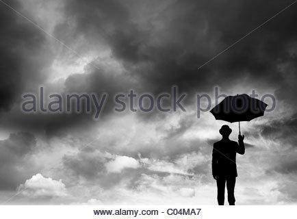 Geschäftsmann hält einen Regenschirm in einem Sturm - Stockfoto