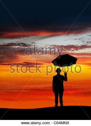 Geschäftsmann hält einen Regenschirm im Sonnenuntergang - Stockfoto