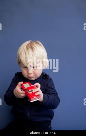 Kleiner Junge mit roten Truck spielen - Stockfoto