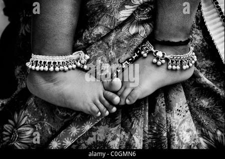 Indische Kinder barfuß gegen Mütter floral Sari. Monochrom - Stockfoto