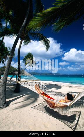 Frau in einer Hängematte unter Palmen an einem Strand auf Peter Island, Britische Jungferninseln, Karibik - Stockfoto