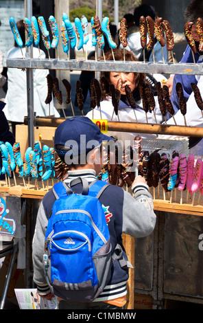 Eine junge Schuljunge genießt Schoko-Bananen an einer Garküche, Ueno-Park, Tokyo JP - Stockfoto