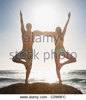 Paar, balancieren auf einem Bein zusammen am Strand - Stockfoto