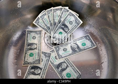 US-Dollar in ein Waschbecken Abfluss. Geld, das Konzept der Abfluss hinunter. - Stockfoto