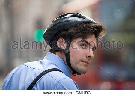Ein Geschäftsmann einen Fahrradhelm tragen pendeln zur Arbeit - Stockfoto