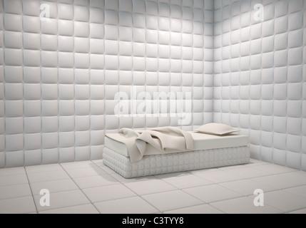 weiße Nervenheilanstalt gepolstert Winkel des Zimmers mit einem Bett - Stockfoto