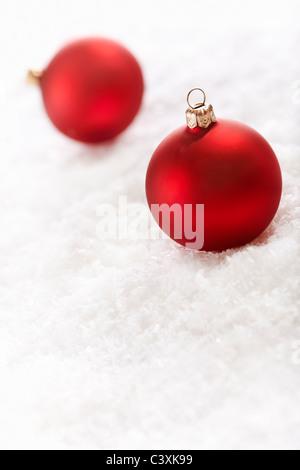 Urlaubsfoto mit roten Kugeln auf dem Schnee Hintergrund, selektiven Fokus - Stockfoto