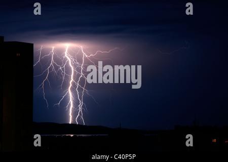 Gewitters schlägt über Stadt und Meer - Stockfoto