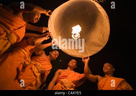 Thailand, Chiang Mai, San Sai.  Mönche starten einen Khom Loi (Himmelslaterne) während der Yi Peng Festival. - Stockfoto