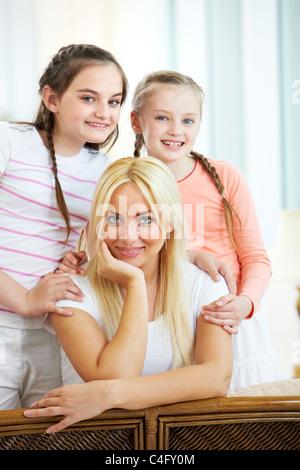 Porträt der glückliche Mutter, als radikalere zwei Töchter beim Blick in die Kamera - Stockfoto