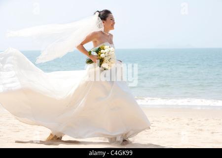 Glückliche Braut laufen am Strand - Stockfoto