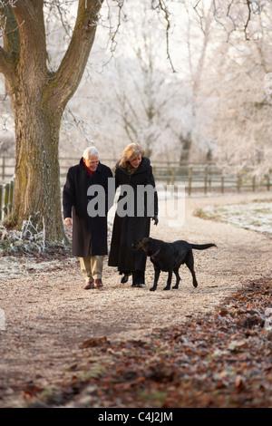 Älteres Paar auf Winter-Spaziergang mit Hund durch frostige Landschaft - Stockfoto