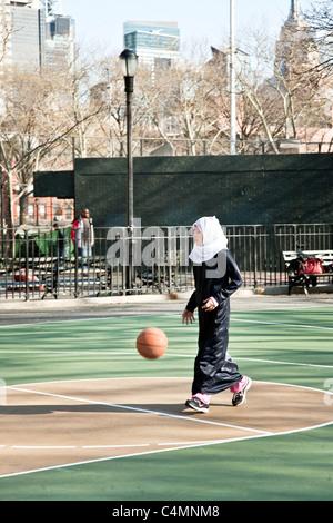 hübsche junges muslimische Mädchen im Kopftuch mit schwarzen Abaya über ihre Jeans spielt mit Fußball in New York - Stockfoto