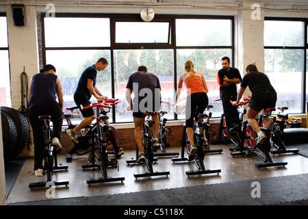 Spinning-Kurs auf stationären Fahrrädern in ein Fitness-Studio - Stockfoto