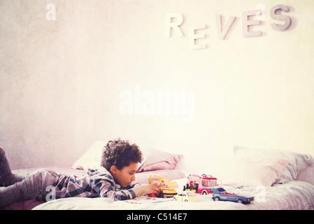 Kleiner Junge liegend auf Bauch im Bett spielen mit Spielzeug-Autos - Stockfoto