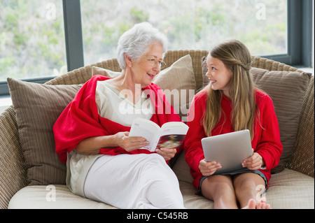 Ältere Frau und ihre Enkelin schauen einander an und Lächeln - Stockfoto