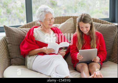 Ältere Frau mit ihrer Enkelin mit einem digitalen Tablet eine Zeitschrift liest - Stockfoto