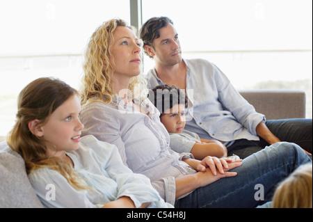 Familie mit drei Kindern auf einer Couch sitzend - Stockfoto