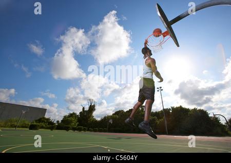 männliche machen Slam Dunk während der Outdoor-Basketball-Spiel, nach oben-Ansicht - Stockfoto