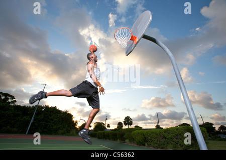 männliche machen Slam Dunk an Outdoor-Basketball-Ziel - Stockfoto