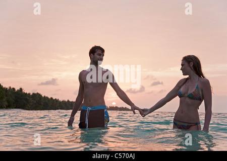 Paar halten Hände mit Wasser am Strand - Stockfoto