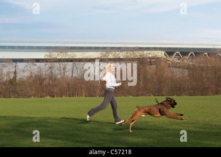 Frau mit Hund im Feld läuft - Stockfoto