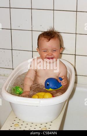 Fröhliche kleine Baby mit Spielzeug, genießen ein Bad in der Badewanne - Stockfoto