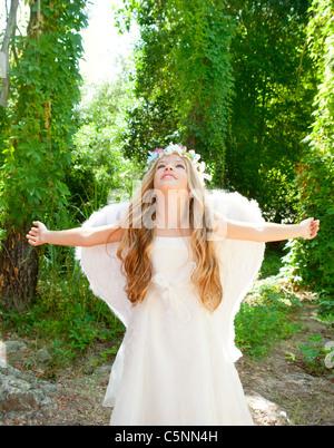 Engel Kinder Mädchen offenen Armen im Wald mit weißen Flügeln und Blumen-Krone - Stockfoto