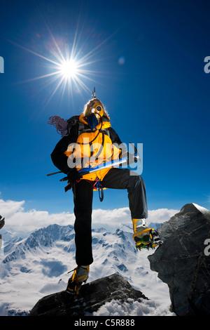 Ein Bergsteiger klettert über die Felsen auf sehr hohen schneebedeckten Berg über den Wolken. - Stockfoto