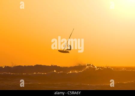 Ein Windsurfer springt eine Ozeanwelle in einem Sonnenuntergang. - Stockfoto