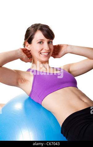 Schöne junge und sportliche Frau, die die Übungen auf einer Fitness-ball - Stockfoto