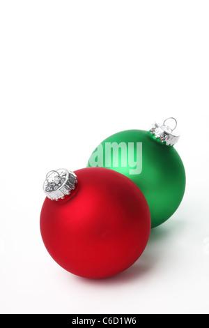 Rote und grüne Weihnachtskugeln auf weißem Hintergrund. - Stockfoto