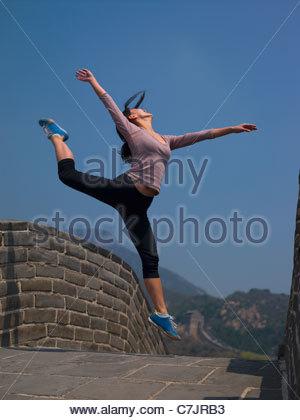 Frau auf der chinesischen Mauer springen - Stockfoto