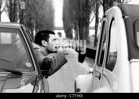 Junger Mann und Frau in zwei verschiedenen Autos - Stockfoto