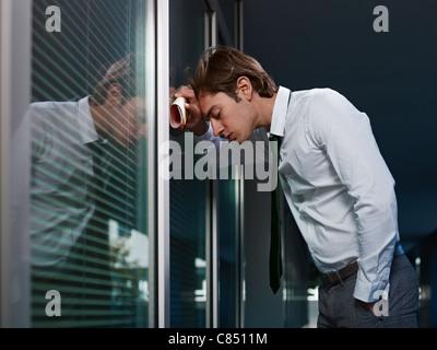 junge Erwachsene italienischen Geschäftsmann schlug mit seinem Kopf gegen ein Fenster im Büro. Horizontale Form, - Stockfoto