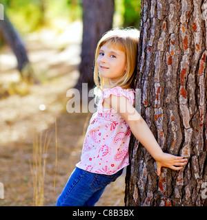 blonde junge Mädchen auf Herbst Baumstamm im Waldpark - Stockfoto