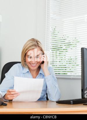 Geschäftsfrau telefonieren und eine Zeitung lesen - Stockfoto