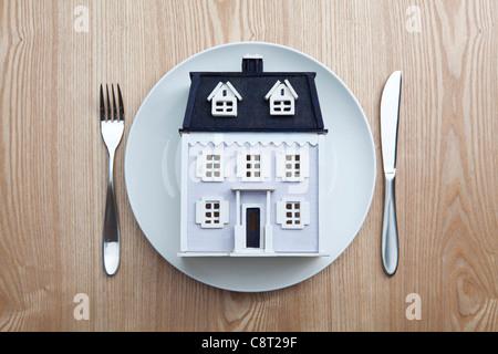 Draufsicht des Musterhauses in Teller mit Gabel und Messer auf den Tisch gelegt. - Stockfoto