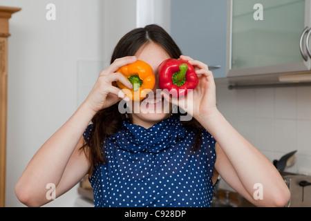 Lächelndes Mädchen spielen mit Paprika - Stockfoto