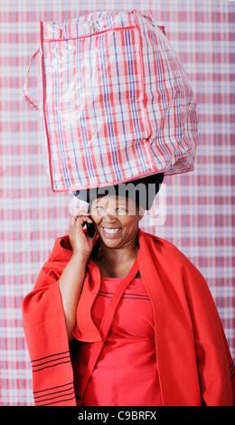 Frau in traditioneller Kleidung Tragetasche mit Handy, Kapstadt, Westkap, Südafrika - Stockfoto