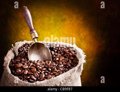Plünderung Kaffeebohnen und Schaufel. Auf einem dunklen Hintergrund. - Stockfoto