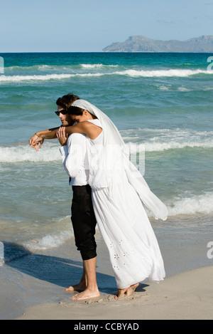Braut und Bräutigam umarmt am Strand - Stockfoto