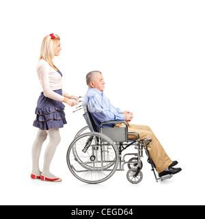 Voller Länge Porträt einer Tochter treibt ihr Vater im Rollstuhl isoliert auf weißem Hintergrund - Stockfoto
